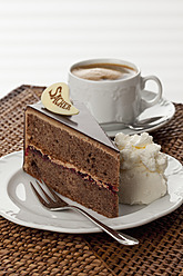 Plate of Sachertorte slice with coffee on straw mat, close up - CSF016289