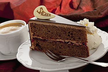 Slice of Sachertorte with coffee cup, close up - CSF016292