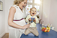 Germany, Bonn, Pregnant mother playing with son in living room, smiling - MFF000485