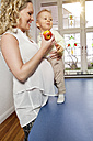 Germany, Bonn, Pregnant mother eating apple with son in living room, smiling - MFF000486