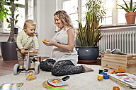 Germany, Bonn, Pregnant mother playing with son in living room, smiling - MFF000517
