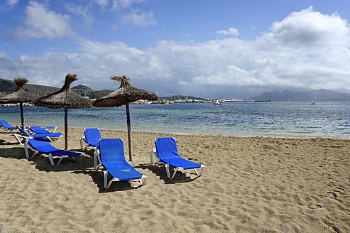 Spain, Empty canvas chair and sunshades on beach at Port de Pollenca - MIZ000203