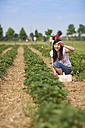 Germany, Bavaria, Young Japanese woman showing strawberry in field - FLF000200