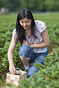 Germany, Bavaria, Young Japanese woman picking strawberries in field - FLF000210