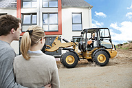 Germany, Neuss, Estate agent driving on wheeled loader on construction site, couple watching house - MFF000471