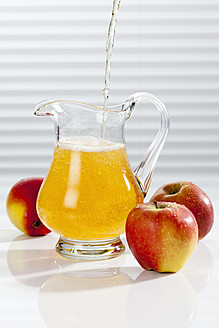Apple juice being poured into pitcher besides apples - CSF016392