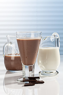 Glass and carafes of chocolate milk and pieces of chocolate, close up - CSF016429