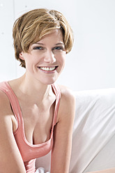 Young woman sitting on couch, portrait, smiling - MAEF005764