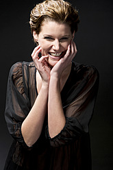 Portrait of young woman against black background, smiling - MAE005774