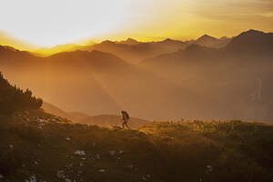 Austria, Salzburg Country, Man hiking through Niedere Tauern mountains at sunrise - HHF004306