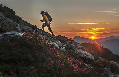 Austria, Salzburg Country, Man hiking through Niedere Tauern mountains at sunrise - HHF004310