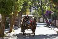 Turkey, Istanbul, Tourist travelling by horse-drawn carriages at Buyukada - SIE003320