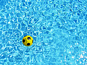 Spain, Football floating on water in pool - SMAF000117