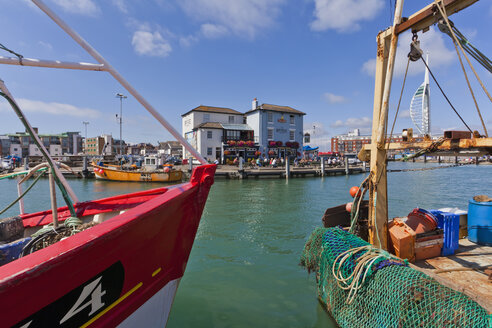 England, Hampshire, Portsmouth, View of fishing boats in harbour and Spinnaker Tower in background - WD001523