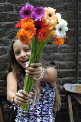 Netherlands, Girl holding flowers in front of brick wall, smiling - MIZ000232