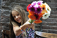 Netherlands, Girl holding flowers in front of brick wall, smiling - MIZ000233