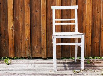 Austria, White chair against brown wooden wall - WVF000318