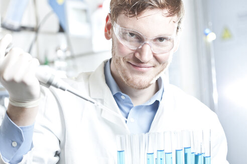 Germany, Young scientist pipetting blue liquid into test tubes, close up - FLF000270