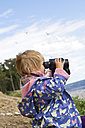 Denmark, Girl looking through binocular at beach - JFEF000019