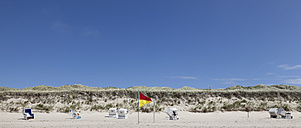 Germany, View of empty beach with roofed wicker beach chairs and flag on Sylt island - ATA000009