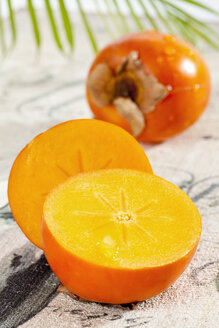 Kaki Persimmon with palm leaf, close up - CSF017445