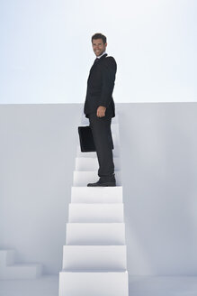 Businessman in black suit with briefcase standing on stairs, smiling, portrait - PDYF000380