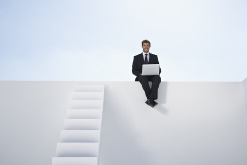 Businessman in black suit sitting on wall and using laptop, smiling - PDYF000389