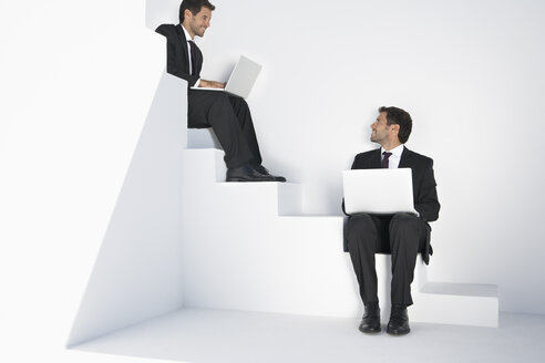 Businessmen sitting on stairs and using laptop - PDYF000410