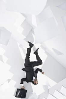 Businessman with briefcase lying down staircase - PDYF000443