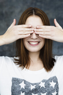Young woman covering eyes, smiling - SPOF000063
