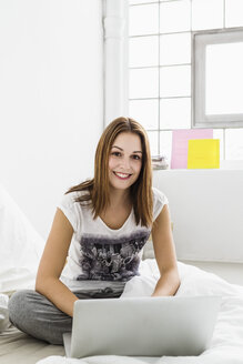 Portrait of young woman using laptop, smiling - SPOF000084