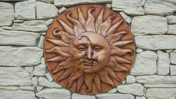 Spain, Ceramic of sun and moon on stone wall at Palau der Saverdera - DJGF000036