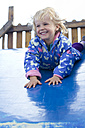 Germany, Girl playing on blue slide, smiling - JFE000066
