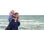 Denmark, Father carrying daughter on shoulder at beach, smiling - JFE000075