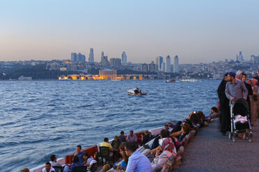 Turkey, Istanbul, People sitting in cafe in Bosphorus, Dolmabahce Palace and Sisli in background - SIE003494