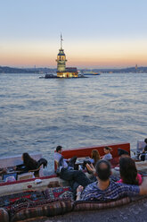 Turkey, Istanbul, People sitting in cafe in Bosphorus, Maidens Tower in background - SIE003497