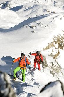 Austria, Men skiing on mountain at Salzburger Land - RN001178