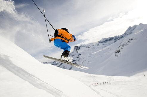 Austria, Man jumping with ski on mountain - RN001182