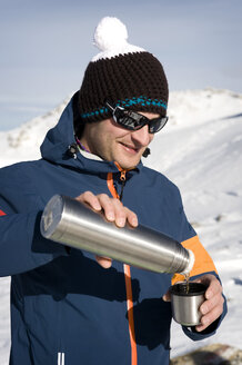 Austria, Man drinking tea, smiling - RN001157