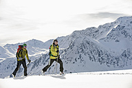 Austria, Man and woman skiing on mountain at Alpbachtal - RN001160