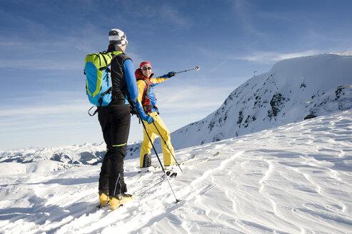 Austria, Men skiing on mountain at Alpbachtal - RN001162