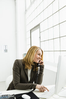 Germany, Businesswoman talking on telephone and using computer, smiling - SPO000118
