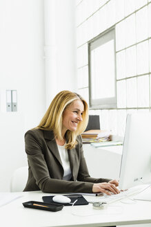 Germany, Businesswoman using computer, smiling - SPO000126