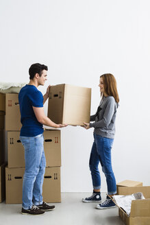 Germany, Munich, Young couple holding cardboard box, smiling - SPOF000239