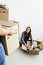 Germany, Munich, Young man holding cardboard box while woman packing box - SPOF000255