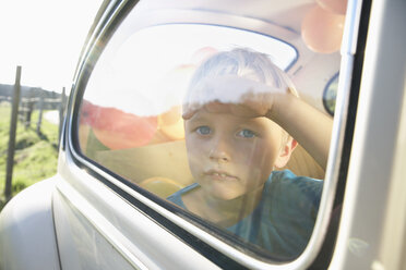 Germany, North Rhine Westphalia, Cologne, Boy in car looking through window - PD000314