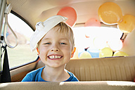 Germany, North Rhine Westphalia, Cologne, Portrait of boy in car with easter bunny mask, smiling - PD000319