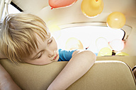 Germany, North Rhine Westphalia, Cologne, Tired boy leaning on car seat - PD000327