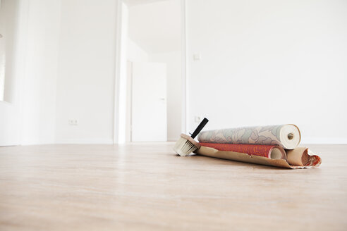 Moving house with rolls of wallpaper on wooden floor - FMKF000519