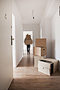 Man unloading cardboard boxes in new house - FMKF000530